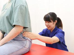 骨盤をチェックする女性施術者