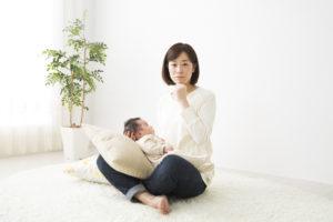 赤ちゃんを抱いて悩む女性